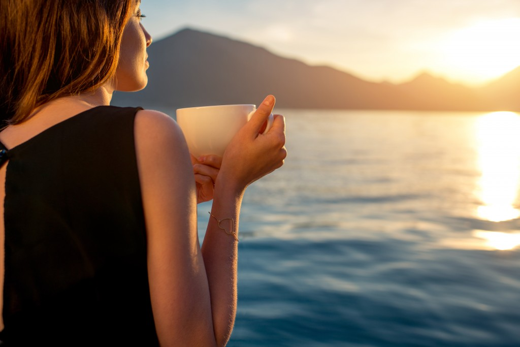 Young woman enjoying coffee on the pier at sunrise with mountains on background